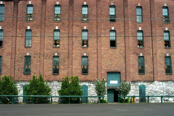 9th century warehouse in Frankfort, Kentucky, United States used to age bourbon whiskey casks, seen closely through the warehouse windows