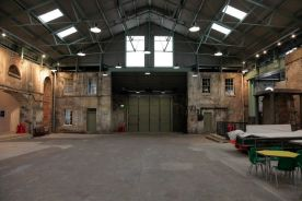 A warehouse, event space with a mix of old warehouse walls and modern white boxes